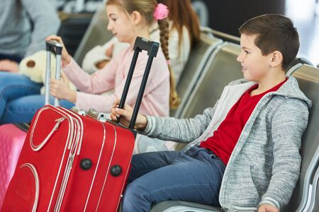Two children with suitcases in the waiting area in the airport terminal are looking forward to the holiday Zdjęcie Seryjne