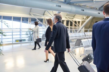 Business people as passengers are in a hurry on their journey in the airport terminal
