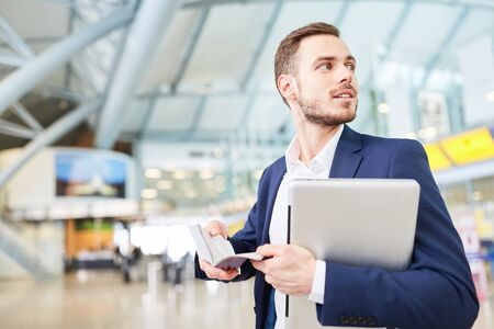 Young businessman on mission in airport terminal with laptop and appointment book Zdjęcie Seryjne