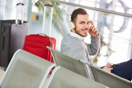 Man in the airport waits for his flight and listens to music with headphones and smartphone