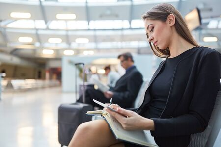 Businesswoman in waiting area in airport with appointment book plans her business trip