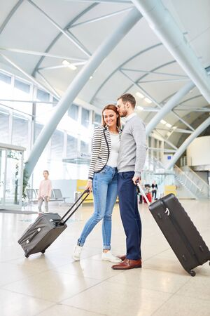 Young couple waiting with suitcases in the airport terminal and looking forward to the holiday together