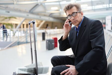 Businessman on duty talking on the mobile phone in airport waiting area