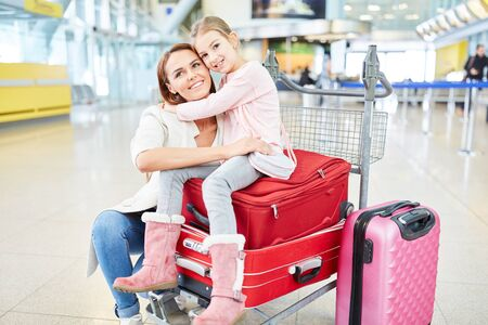 Mother and child with a lot of luggage in the airport terminal travel together on vacation Zdjęcie Seryjne