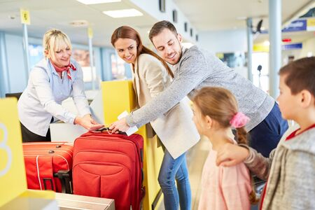 Family and airport staff at the baggage check of suitcases in the airport terminal Zdjęcie Seryjne