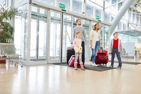 Family with two children and luggage in the airport terminal is looking forward to the holiday