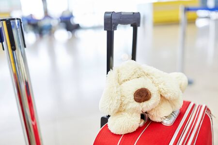 A cuddly toy lies on a wheeled suitcase in the airport terminal