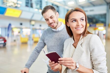 Young couple in the airport terminal with travel documents waiting for the connecting flight Zdjęcie Seryjne