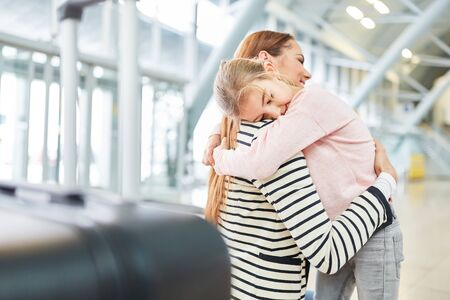 Mother and daughter hug each other in the airport terminal when they meet again after a trip Zdjęcie Seryjne