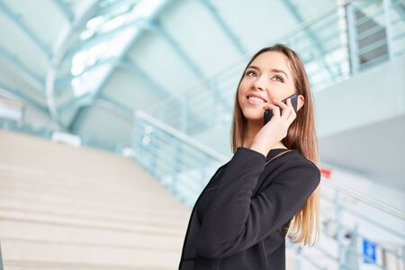 Young businesswoman on business trip is phoning with smartphone in airport terminal Zdjęcie Seryjne