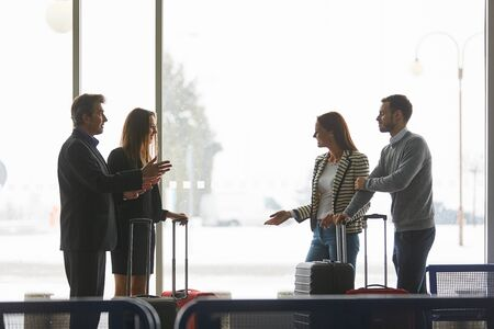 Group of travelers and couples talking in the waiting area in the airport terminal