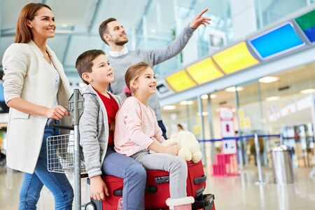 Family and children in the airport with luggage when changing trains looking forward to the departure