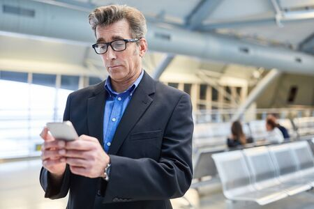 Businessman is amazed at a message on the smartphone in the airport terminal