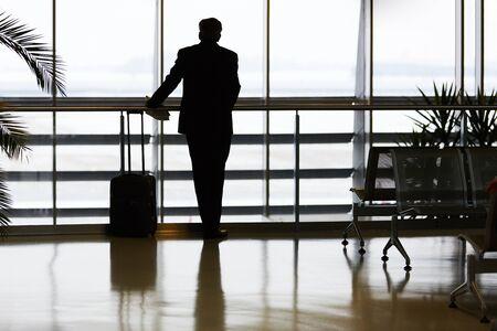 Hombre de negocios en viaje de negocios en la terminal del aeropuerto espera el vuelo en la escala