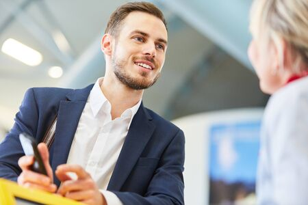 Young Businessman As Traveler At Check In Or Baggage Drop Off With Smartphone