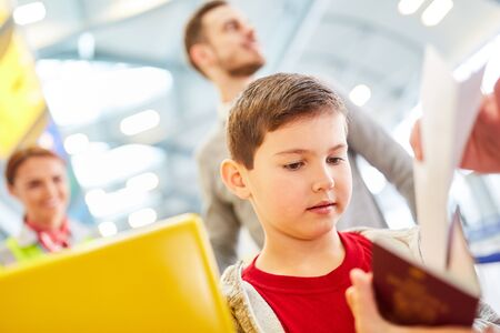 Boy looks in his passport at the airport check-in just before departure on vacation