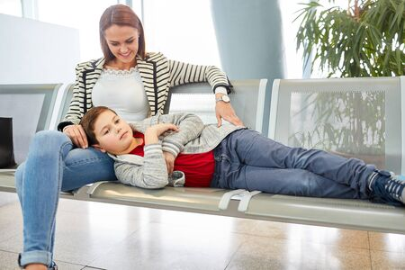 Mother and son in the rest area in the airport are waiting for departure and are bored