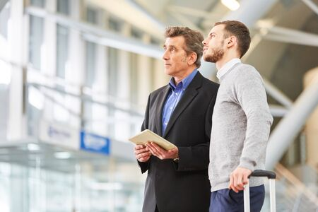 Two businessmen or managers in airport terminal using tablet computer before business trip