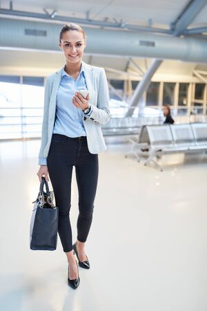 Young business woman using smartphone on business trip on the way in airport terminal
