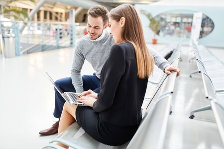 Business people in front of a business trip with laptop PC in waiting area in airport terminal