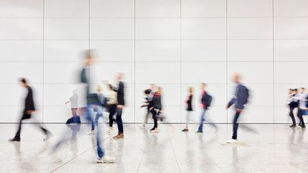 Anonymous blurred business people rush through trade fair hall or airport