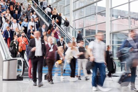 Many people and people on escalator at a business trade fair
