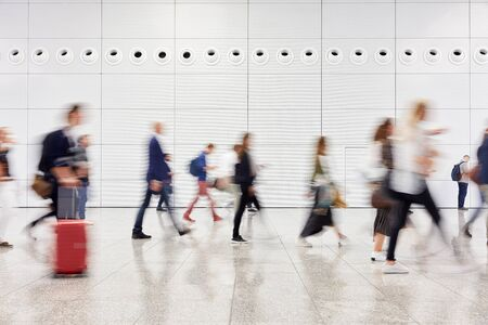 Many anonymous blurred business people traveling in the airport or at a trade fair