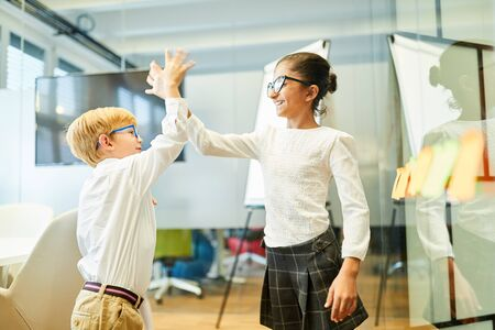 Two business kids as successful business partners celebrate deal with high five