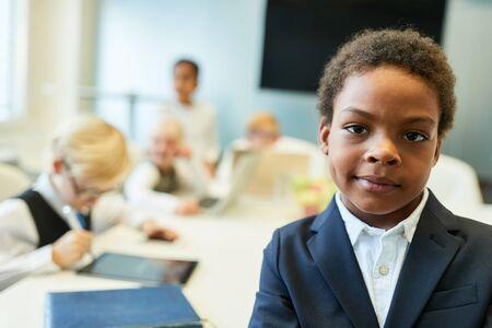 Afrikanisches Kind als Geschäftsmann oder Unternehmer vor seinem Geschäftsteam