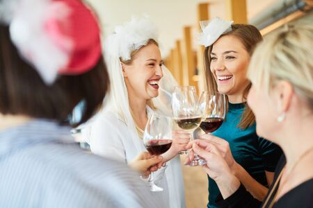 Women drink a glass of red wine with the bride at hen party
