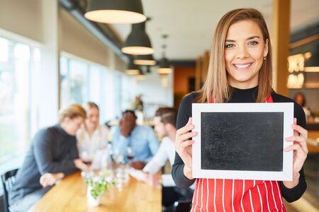 Junge Kellnerin oder Kellnerin hält eine leere Kreidetafel im Restaurant