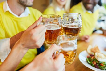 Hands hold beer glass while toasting in a bar or restaurant Zdjęcie Seryjne