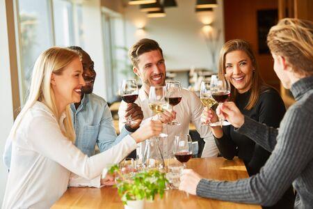 Un groupe d'amis boit du vin et fait la fête ensemble au restaurant ou au bar Banque d'images