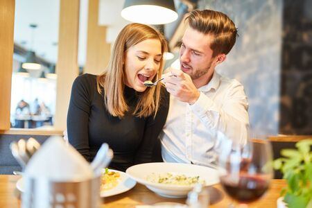 Young man lovingly feeds his girlfriend during a rendezvous in the restaurant Standard-Bild
