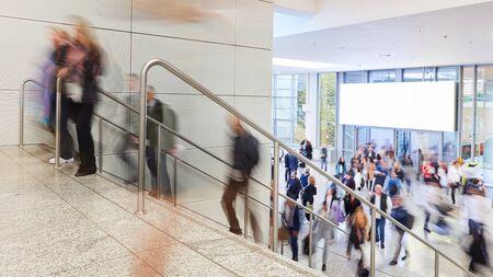 Molte persone anonime stanno camminando su una scala davanti a un poster web in una fiera Archivio Fotografico