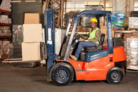 Worker transports delivery with forklift in shipping center