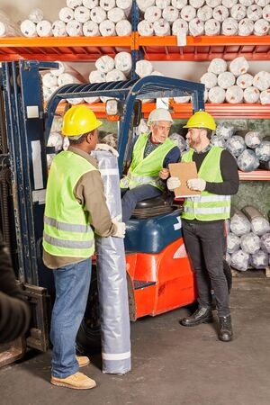 Logistics workers and forklift drivers work together in the shipping warehouse