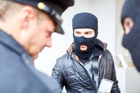 Un policier ou un agent de sécurité contrôle deux cambrioleurs masqués