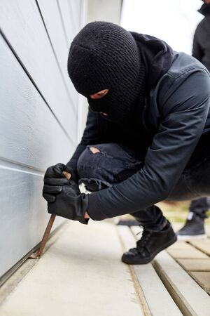 Burglar with crowbars at the gate of a garage or warehouse Banque d'images