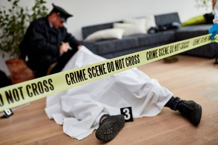 Policeman next to dead body investigating murder at crime scene