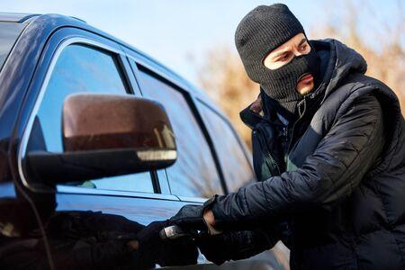 Autodieb bei Autodiebstahl steht vor der Autotür Standard-Bild
