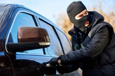 Car thief in car theft is at the car door Stock Photo
