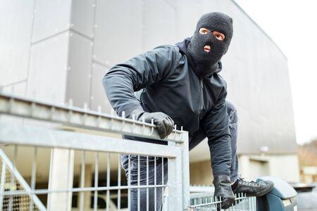Un cambrioleur masqué escalade une clôture lors d'un cambriolage