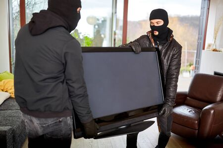 Two hooded burglars steal televisions as loot from a living room Stok Fotoğraf
