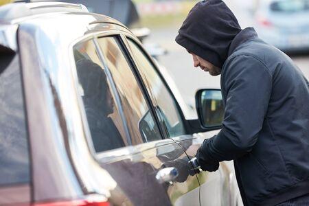 Car thief stealing a car at the car door