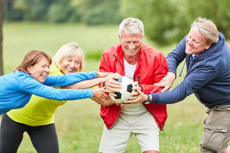 Active seniors struggle with each other for a football in the park and have fun Stok Fotoğraf