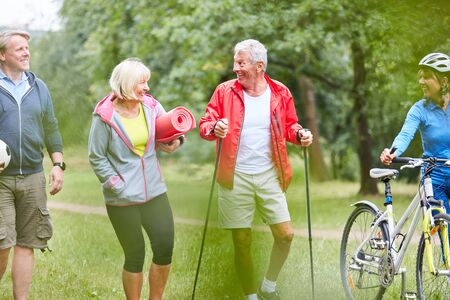 Active seniors in the sports club work together in nature