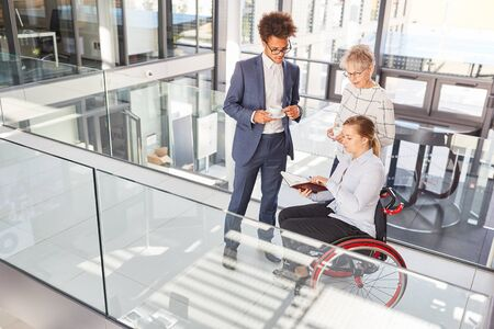 Inclusion and diversity in the business office with a businesswoman in a wheelchair Banque d'images