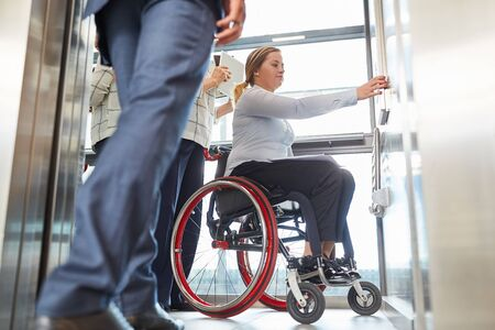 Woman as a wheelchair user presses elevator button for inclusion and accessibility Stock Photo