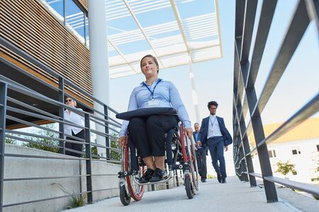 Business woman in a wheelchair in front of the office on a ramp with other workers